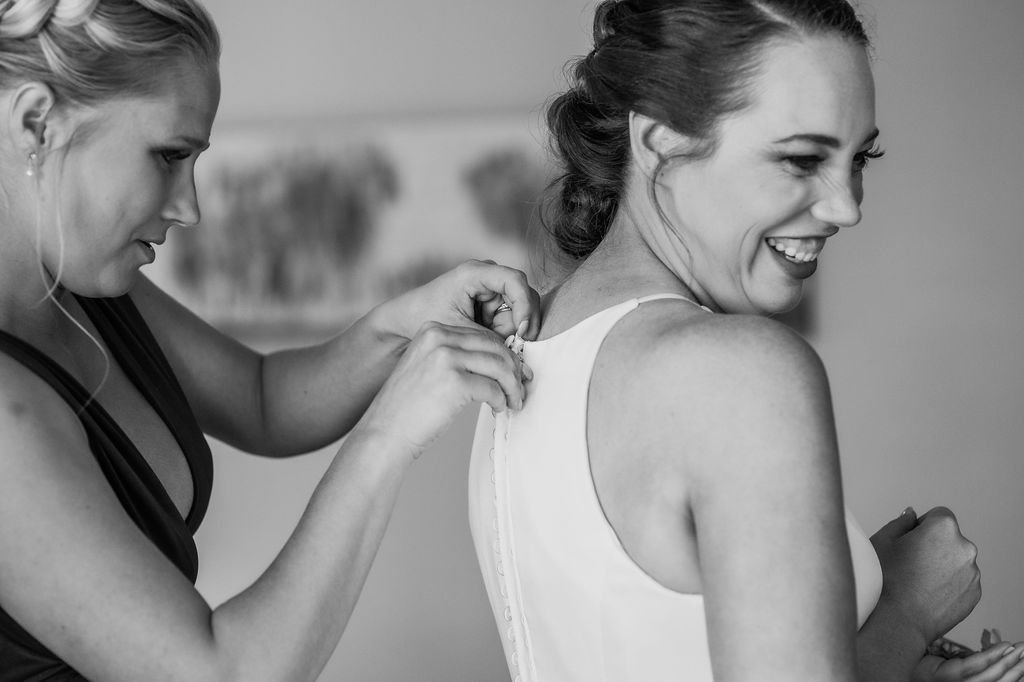 bride and maid of honor getting ready for wedding