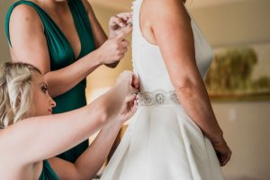 wedding day preparations, bride and bridesmaids getting ready, buttoning up bridal dress