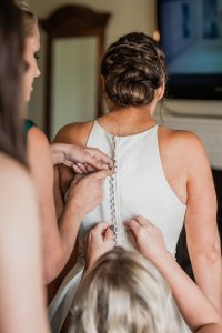 twisted bridal updo, buttoning up wedding dress, bridesmaids and bride getting ready