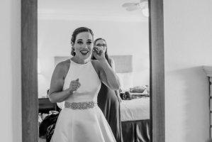 bride putting on earrings, wedding day preparations, a line wedding dress, crystal wedding dress, updo bridal