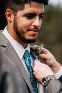 putting on groomsmen's boutonnière, white and green flowers, teal tie, light gray suit