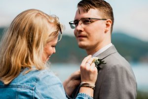 putting on groomemen's boutonnière, white and green flowers