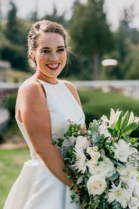 smiling bridal portrait, classic bridal style, a line dress, high neckline wedding dress, white green wedding bouquet, wedding up do