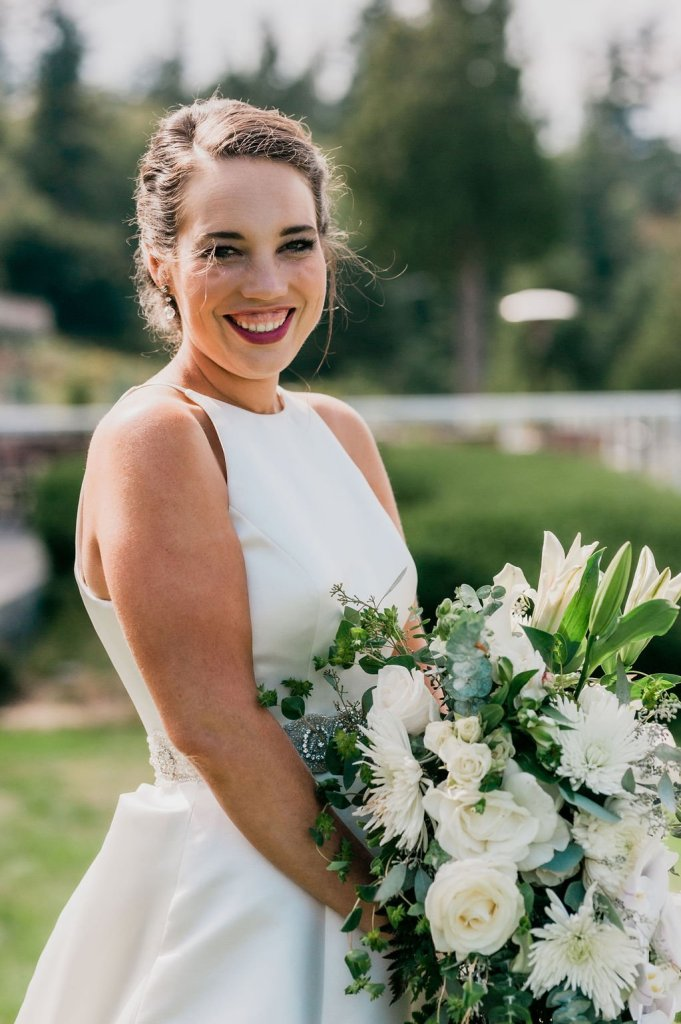smiling bridal portrait, classic bridal style, a line dress, high neckline wedding dress, white green wedding bouquet, wedding up do