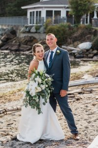 bride and groom laughing on beach at Pacific Northwest wedding, green and white wedding, gray suit, high neckline wedding dress