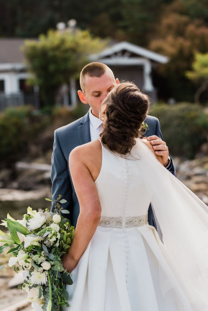 wedding hair ideas, twisted updo, bride and groom kissing on beach
