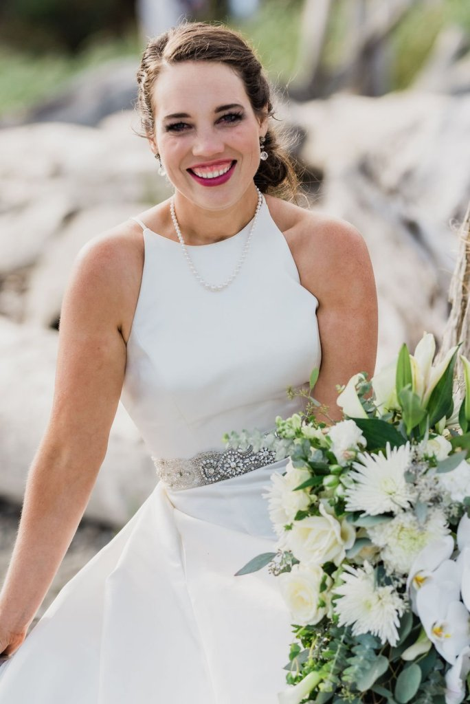 smiling bride on beach in classic wedding dress, pearl necklace, crystal earrings, white and green wedding flowers, Pacific Northwest wedding portraits