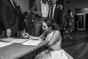 bride signing marriage certificate at wedding