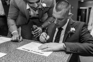groom signing wedding certificate at wedding