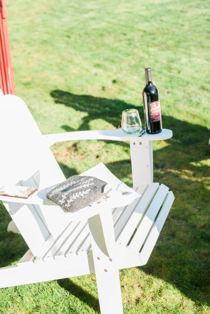 Adirondack chair with wine and needlepoint in backyard
