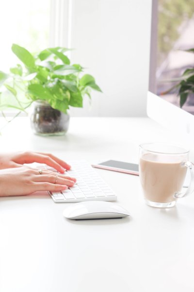 unique and easy ways to make money from home, woman working from home on a desktop apple computer with an oat milk latte and houseplants