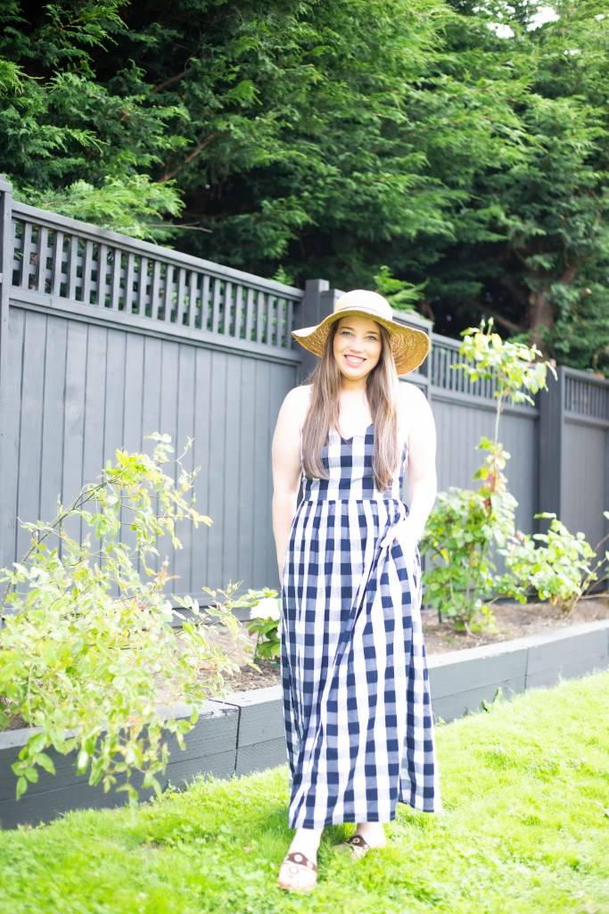 woman in gingham maxi dress and sunhat summer outfit with black fence and white flowers in garden
