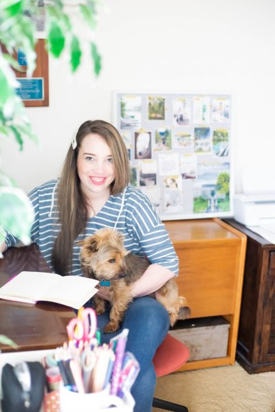 Yorkiepoo and woman sitting in an office