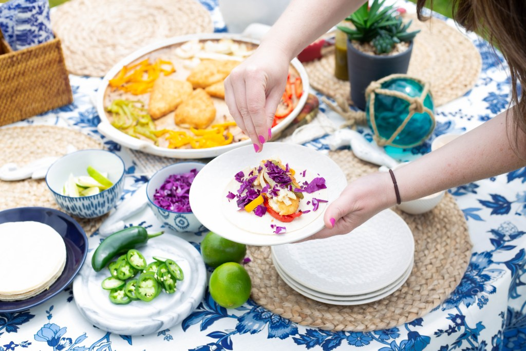 making a fish taco outside wit beautiful summer tablescape