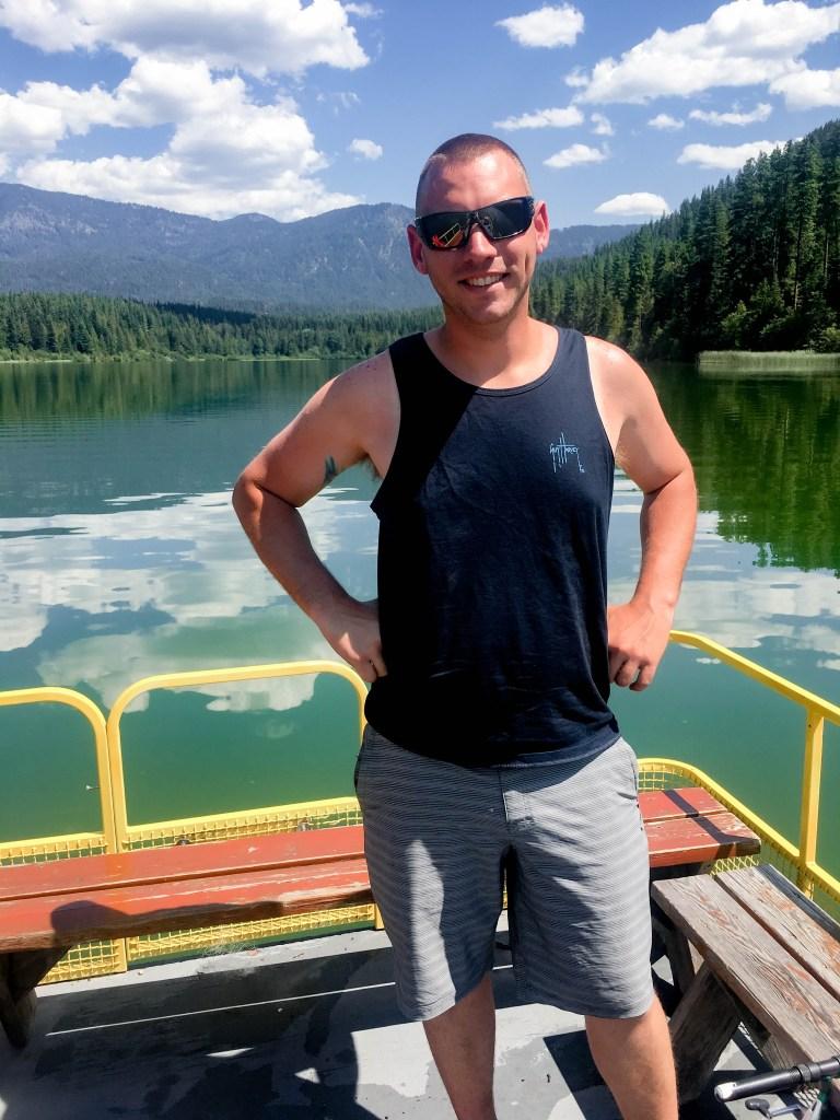 Man on pontoon boat on lake smiling