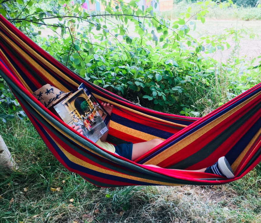 Boy reading book in hammock at Timber Festival