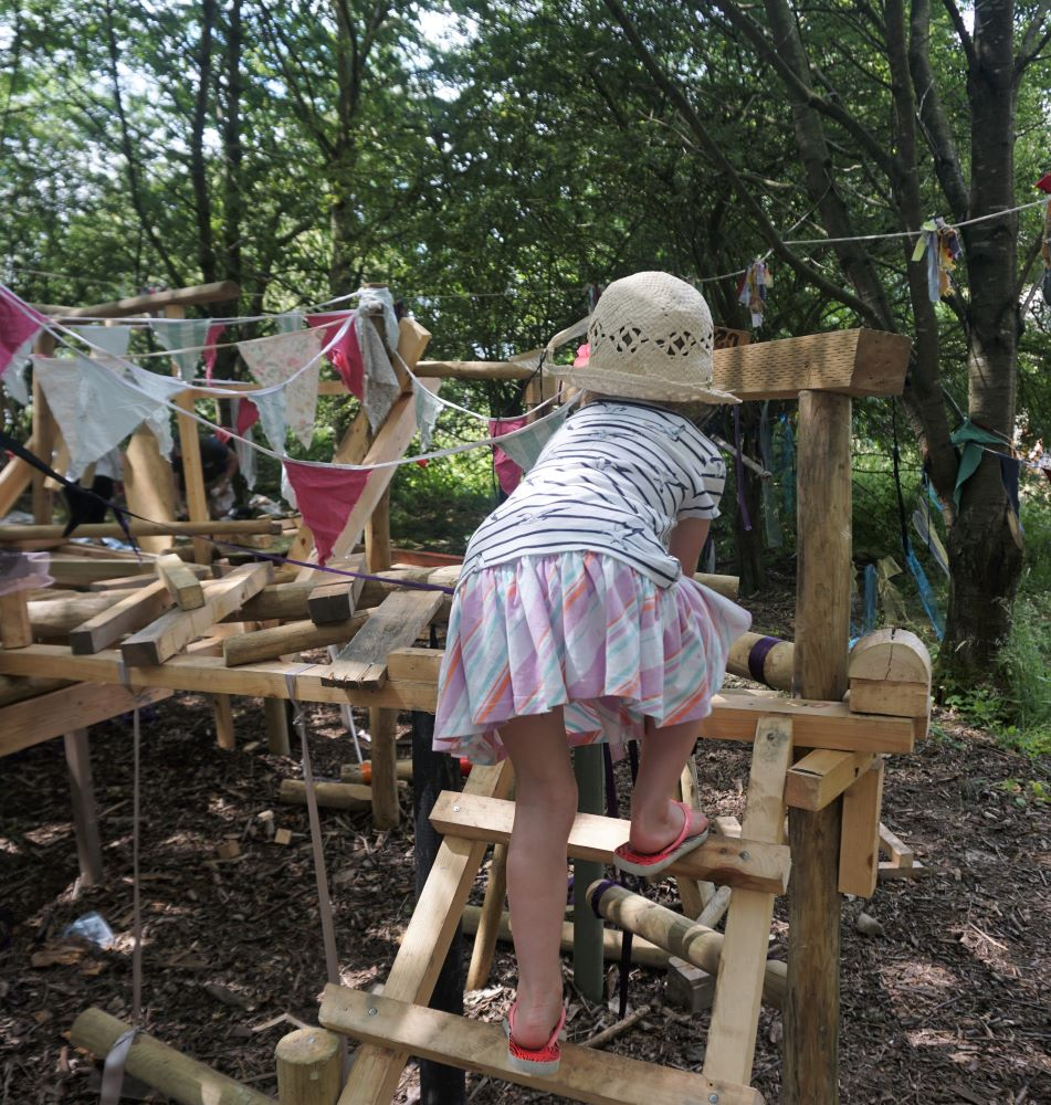 Girl climbing a wooden playground at Timber Festival in the National Forest
