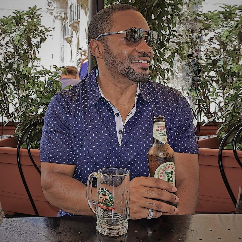 Celebrity musician producer social influencer Official Tyrone Smith in Palermo Sicily enjoying a Birra Moretti wearing Banana Republic, LaPrairie, Louis Vuitton