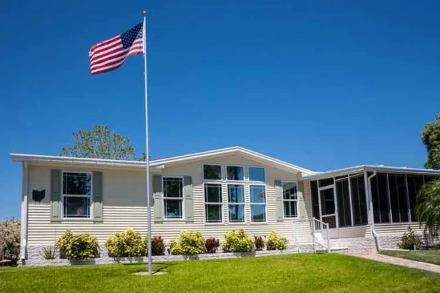 Mobile home with American flag, front lawn and clear blue sky.