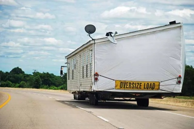 Half of double-wide house trailer being transported along interstate highway.