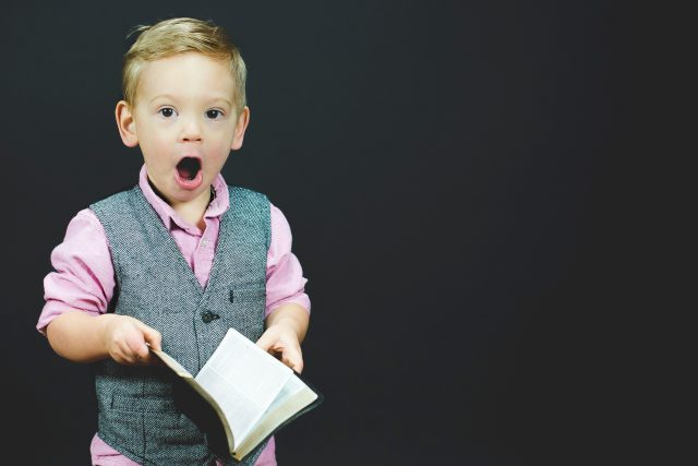 Image: little boy holding a book, looking shocked