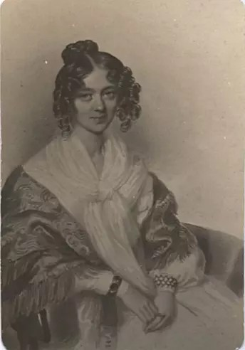 Zdjęcie młodej kobiety z mocno kręconymi lokami siedzącej na fotelu.