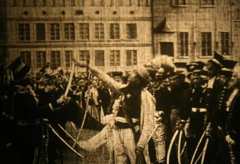 Niewyraźny kadr w w kolorach sepii. Kościuszko z uniesioną ręką dotyka trzymanej przez żołnierza szabli i zapewne składa pzysięgę.