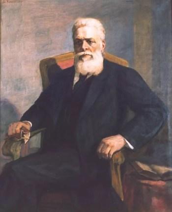 Portret starszego mężczyzny o siwych włosach i bujnej siwej brodzie siedzącego w czarnym stroju na fotelu z rękoma na oparciach.