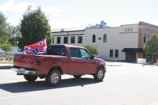 Two white males drive down Queen Street in downtown Kinston on
