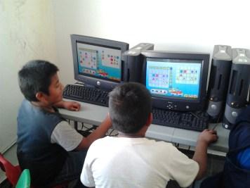 Hermanos trabajando juntos en resolver un Puzle de GCompris.