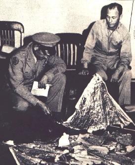 Oficiales de la U.S. Air Force observando restos del globo sonda que fue puesto en lugar del OVNI siniestrado en Roswell.