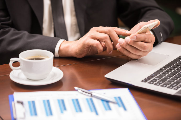 Mann sitzt an einem Tisch in einem Restaurant und tippt in sein Handy, davor eine Tasse Kaffee, ein Blatt mit Diagrammen und ein Laptop. Detektiv Hannover