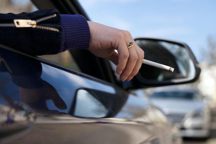 Frau hält Zigarette aus dem Auto; Kurtz Detektei Essen
