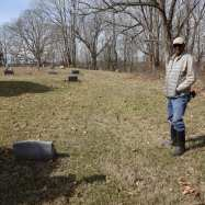 Harry Ivory stands next to his family's headstones.
