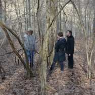 Harry, Lydia, and Jacob in conversation in the woods behind the cemetery.