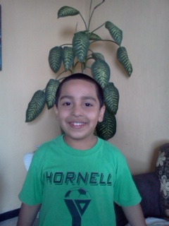 Jairo, age 7, has already assumed the role as protector of the family and the man of the house.