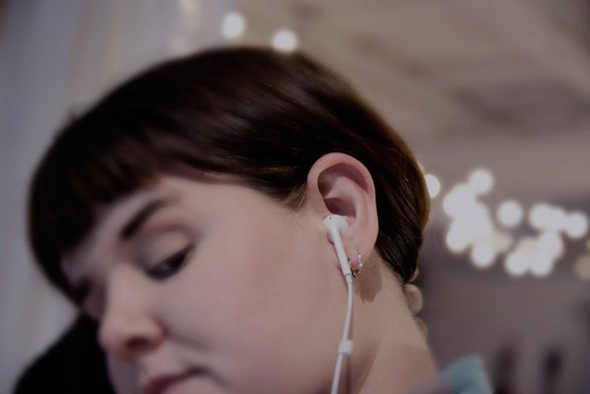 Kvinna med hörlur i örat lyssna på podcast komma igång bästa appen tips bra podcasts på svenska