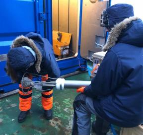 Co-Chief Scientist Ben Rabe is holding the MSS while Physical Oceanographer Sandra Tippenhauer rinses off the sensors with fresh water to prevent salt crystals from forming.