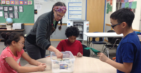 Tedesche helps elementary school students build a groundwater model in a box in the village of Unalakleet on the Bering Sea, Alaska. (Photo by S. Kieper)