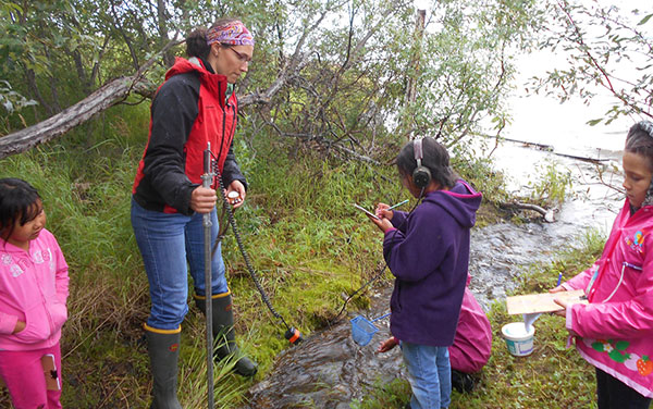 Tedesche helps Girl Scouts use a current meter to find out how fast a village stream flows into Six Mile Lake in the village of Nondalton, Southwest Alaska. (Photo by A. Gore)