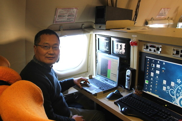 Zhang works on in-situ dropsonde observations on board the WP-3D. (Photo by M. Wang)
