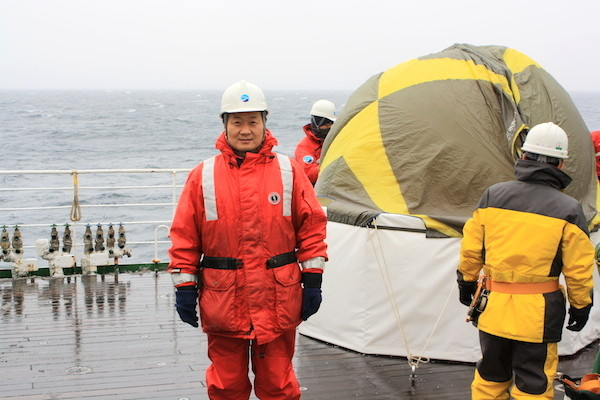 Zhang on the research vessel Mirai. Behind is a tent containing an ozonesonde, an instrument for measuring the atmospheric concentration of ozone and other gases, which he and his colleagues are preparing to launch. (Photo courtesy of Xiangdong Zhang)