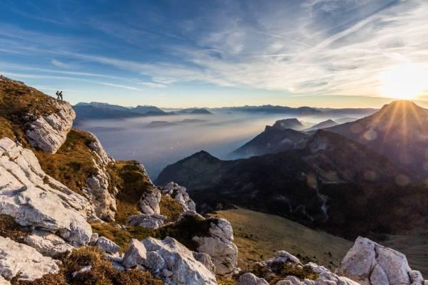Deux randonneurs contemplent la ville de Grenoble depuis les flancs de la Dent de Crolles au soleil couchant