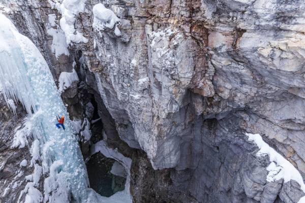 Un alpiniste en solo sur le Tokkum Pole, un pilier de glace au fond du Marble Canyon, Alberta, Canada