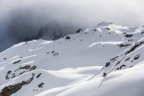Un Skieur File Dans Un Rayon De Soleil Dans Les Aiguilles Rouges, Au Fond Les Aiguilles De Chamonix Dans La Tempete