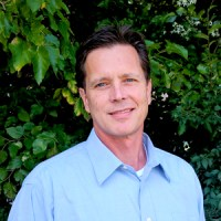 Portrait of UC-B's Director of Construction: caucasian man in blue shirt again leafy green background.