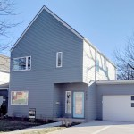 Exterior view of modern two story house with small covered porch and attached garage.