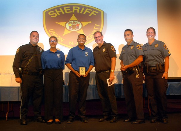 Union County Sheriff Joseph Cryan joined Renee Froehlich-Garcia of Roselle Park as she presented the 2015 Ralph Froehlich Perseverance Award to Anthony Davis of Plainfield during the 8th Annual Union County Sheriff's Youth Police Academy Graduation at Rahway High School Performing Arts Center. Renee Froehlich-Garcia is the granddaughter of the late Union County Sheriff Ralph Froehlich for whom the award is named. They were joined by academy instructors Anthony Chodan from the Elizabeth Police Department, Union County Sheriff's Officer Kenny Gerhart and Sgt. Tara Halpin. Approximately 75 teens took part in the graduation ceremony.