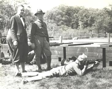 Park Commissioner Charles Hansel firing at the opening of the Union County Rifle Range. Standing are W.R. Tracey, Engineer and Secretary and Colonel John Martin. May 1930
