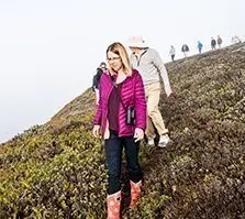 woman in pink jacket and man in hat and sweater walk down a steep slope with green vegetation